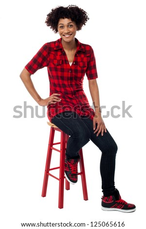 Studio shot of a relaxed young woman sitting on red stool.