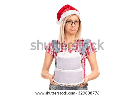 Studio shot of a sad woman with Santa hat holding a cake and looking at the camera isolated on white background - stock photo