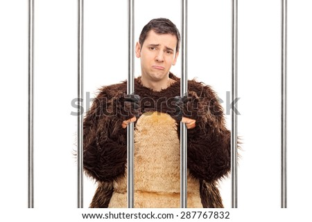 Studio shot of a sad young man in a bear costume standing behind bars in a cell isolated on white background - stock photo
