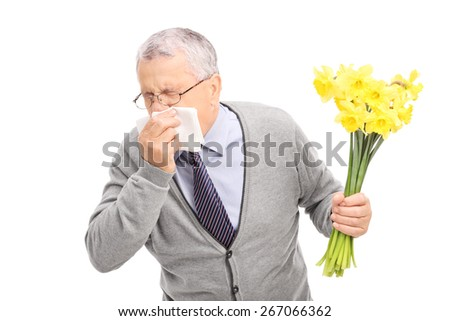 Studio shot of a senior having an allergic reaction to flowers and sneezing on a napkin isolated on white background - stock photo