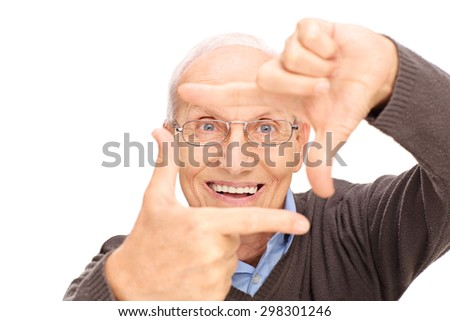 Studio shot of a senior man framing a photo with his fingers and looking at the camera isolated on white background - stock photo