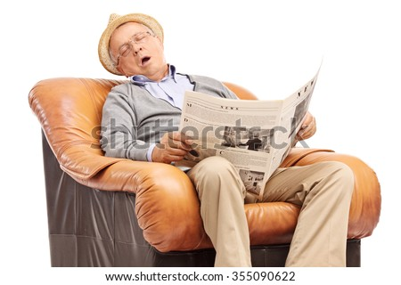 Studio shot of a senior man sleeping on an armchair and holding a newspaper in his hands isolated on white background - stock photo