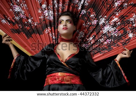 Studio shot of a sexy geisha holding a huge fan. Low angle. - stock photo