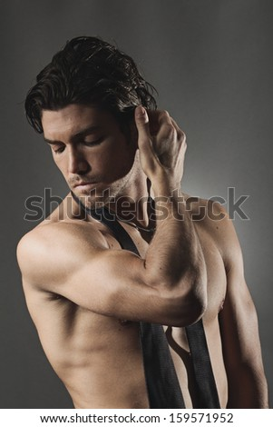 Studio shot of a sexy man posing shirtless . Grey backdrop portrait - stock photo