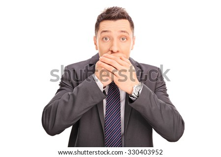 Studio shot of a shocked young businessman covering his mouth and looking at the camera isolated on white background - stock photo