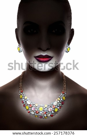 Studio shot of a silhouette of a young girl with red lips wearing jewelry