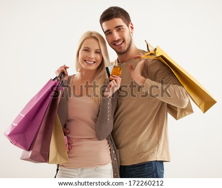 Studio shot of a smiling Caucasian couple holding shopping bags. - stock photo
