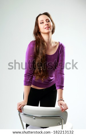 Studio shot of a thoughtful woman with her knee up on a office chair over gray background - stock photo