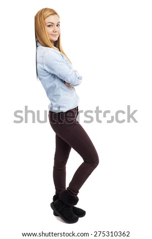 Studio shot of a trendy beautiful teenage girl with arms folded leaning against the wall isolated over white background - stock photo