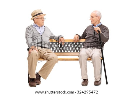 Studio shot of a two senior men arguing with each other seated on a wooden bench isolated on white background - stock photo