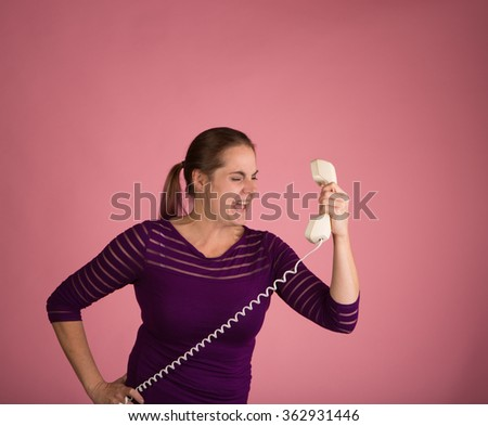 Studio shot of a woman on a pink background with a vintage corded phone having an angry conversation - stock photo