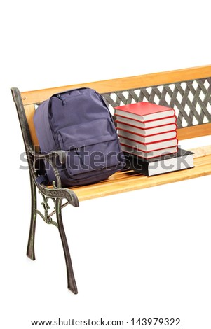 Studio shot of a wooden bench with books and school bag on it, isolated on white background - stock photo