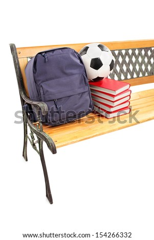 Studio shot of a wooden bench with books, school bag and football on it, isolated on white background - stock photo