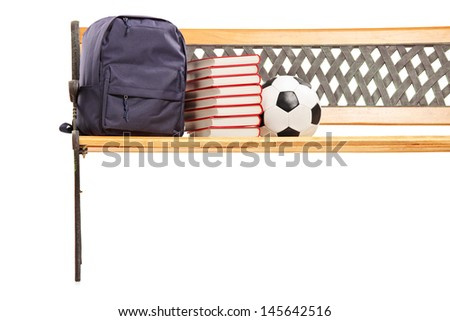 Studio shot of a wooden bench with books, school bag and soccerball on it, isolated on white background - stock photo