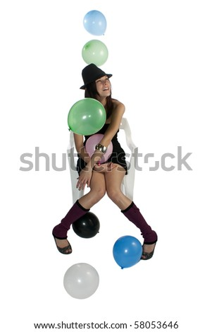 Studio shot of a young and beautiful woman with a black dress and hat, sitting on a white chair with balloons, isolated on white. - stock photo
