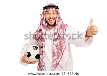 Studio shot of a young Arabian male holding a football and giving a thumb up isolated on white background - stock photo