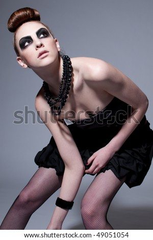 Studio shot of a young, beautiful, fashion model with black make-up, dress and beads - stock photo