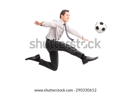 Studio shot of a young businessman kicking a football and smiling isolated on white background - stock photo
