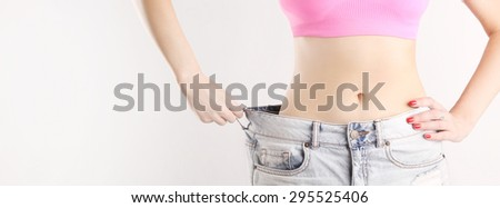 Studio shot of a young caucasian fit female wearing big jeans after diet - stock photo