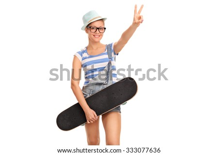 Studio shot of a young female skater holding a skateboard and making peace hand gesture isolated on white background - stock photo