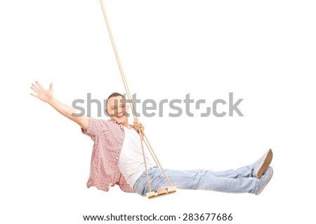 Studio shot of a young joyful man swinging on a swing and gesturing happiness isolated on white background - stock photo