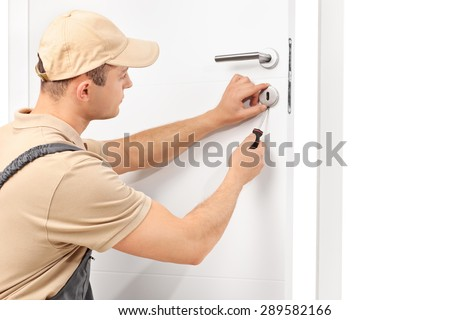 Studio shot of a young male locksmith installing a lock on a white door with a screwdriver isolated on white background - stock photo