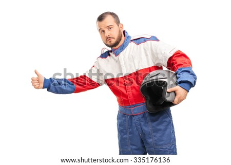 Studio shot of a young man in a racer suit holding a helmet and hitchhiking with his thumb isolated on white background - stock photo