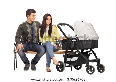 Studio shot of a young parents sitting on a wooden bench with a baby stroller beside them isolated on white background - stock photo