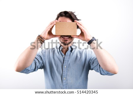 studio shot of a young, smiling model looking through cardboard virtual reality (VR) headset, isolated on white