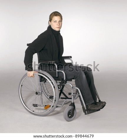 studio shot of a young woman in a wheelchair in light grey back - stock photo