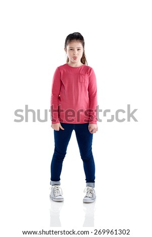 Studio shot of adorable little girl sticking out her tongue to camera while standing over white background - stock photo