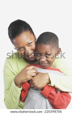 Studio shot of African mother hugging her young son - stock photo