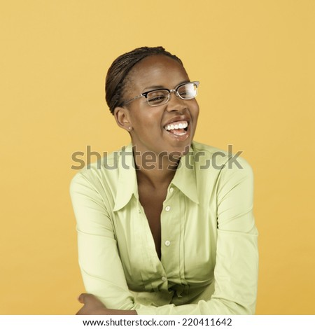 Studio shot of African woman wearing eyeglasses and smiling - stock photo