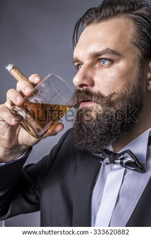 Studio shot of an elegant young man with retro look smoking a cigar and drinking whiskey over gray background - stock photo