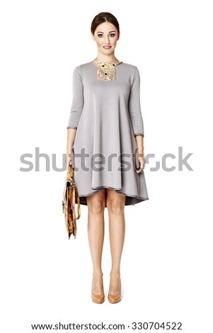 Studio shot of an elegant young woman standing against a white background. - stock photo