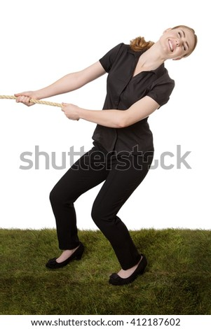 Studio shot of an office business worker standing on grass, pulling on a large rope in a tug of war.  Isolated on white - stock photo