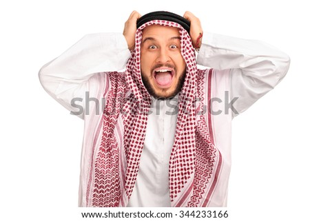Studio shot of an outraged young Arab posing with his hands on his head isolated on white background - stock photo