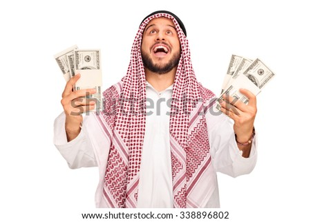 Studio shot of an overjoyed Arab holding stacks of money and looking up isolated on white background - stock photo