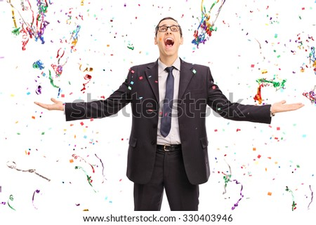 Studio shot of an overjoyed businessman standing in the middle of a lot of confetti streamers isolated on white background - stock photo