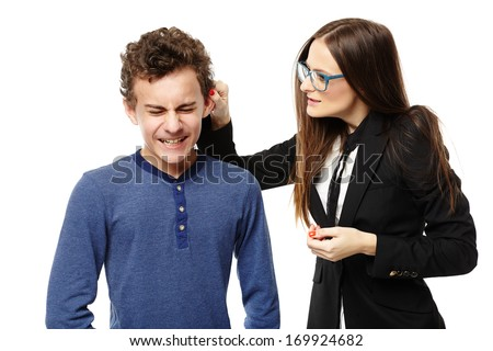 Studio shot of angry teacher grabbing student's ear, isolated over white background - stock photo