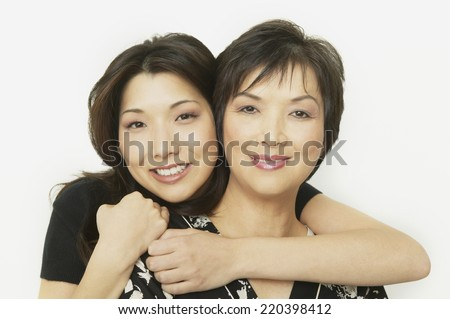 Studio shot of Asian mother and adult daughter hugging - stock photo