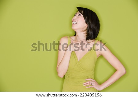 Studio shot of Asian woman looking up and laughing - stock photo