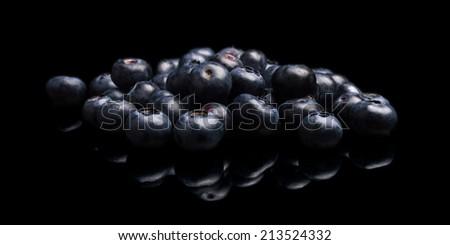 Studio shot of assortment fresh blueberries isolated on black background - stock photo
