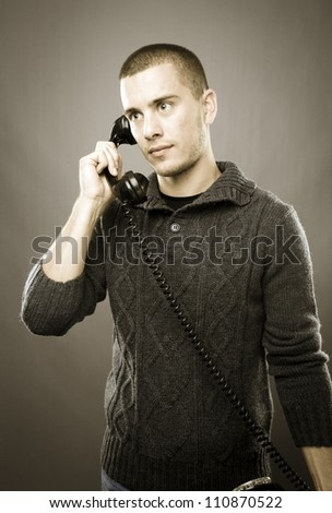 Studio shot of attractive man with old phone - retro style