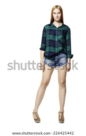 Studio shot of attractive young woman in shirt and shorts. - stock photo