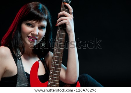 Studio shot of attractive young woman with electric guitar, black background - stock photo