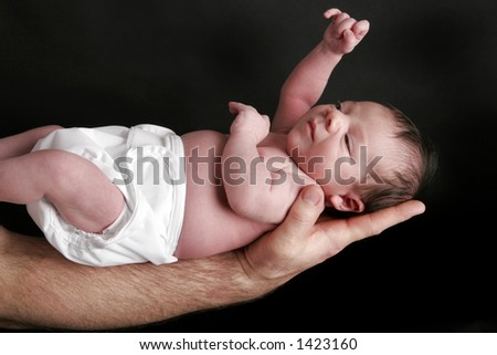 Studio shot of baby being held in a man's  arm with black background - stock photo