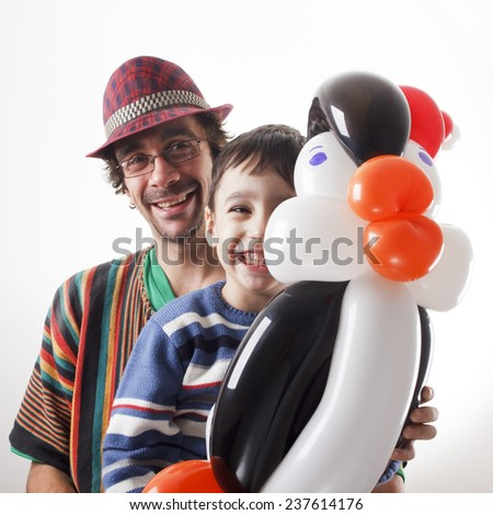 Studio shot of balloon twister and little boy with penguin. - stock photo