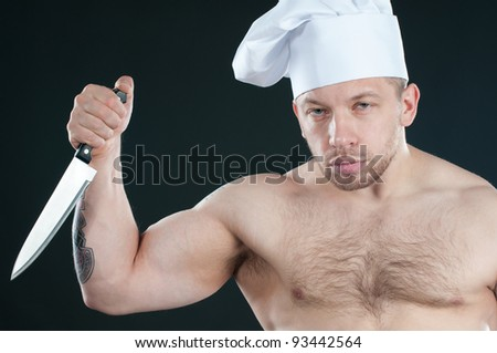 Studio shot of bare torso chef with a kitchen knife, dark background - stock photo