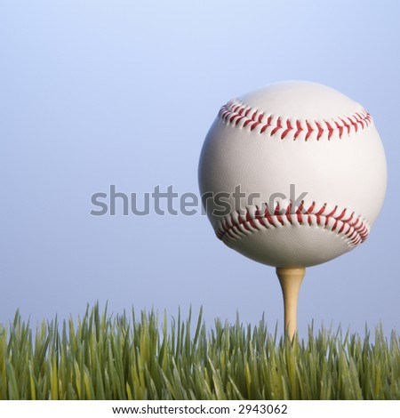 Studio shot of baseball resting on golf tee in grass.